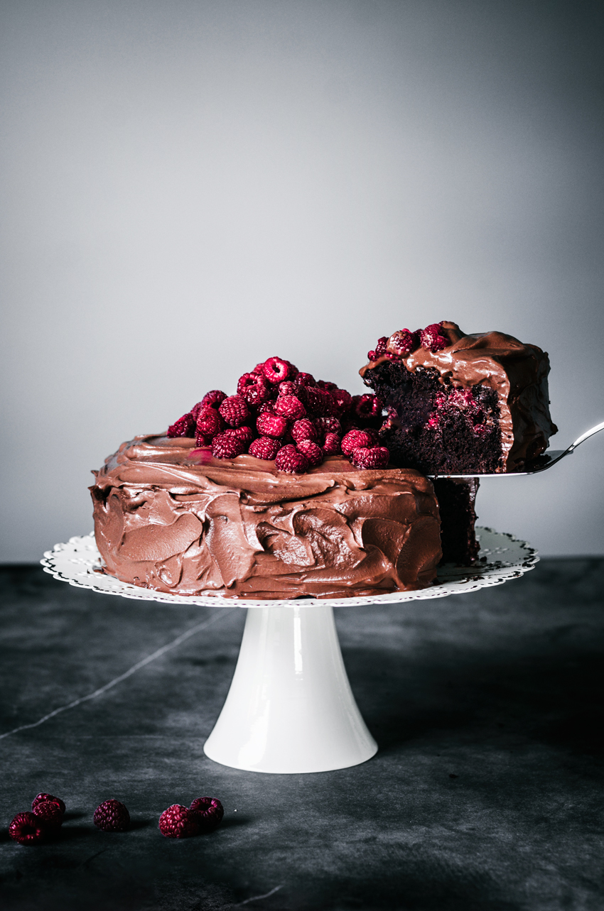 Chocolate ganache iced cake on white cake stand with pile of raspberries on top, one slice being lifted.