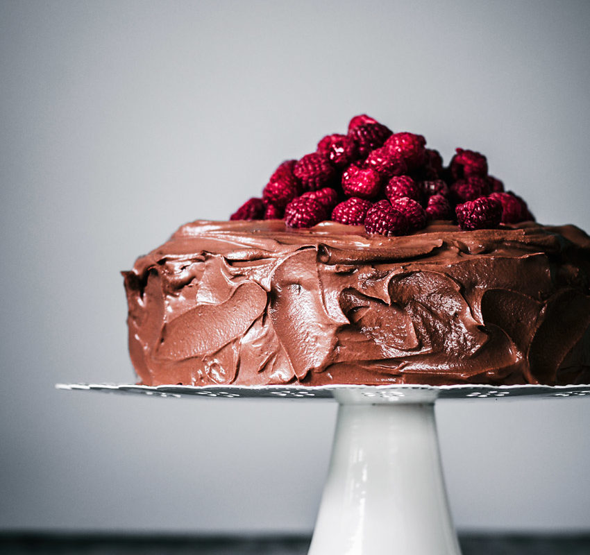 Chocolate raspberry cake with pile of berries on top.