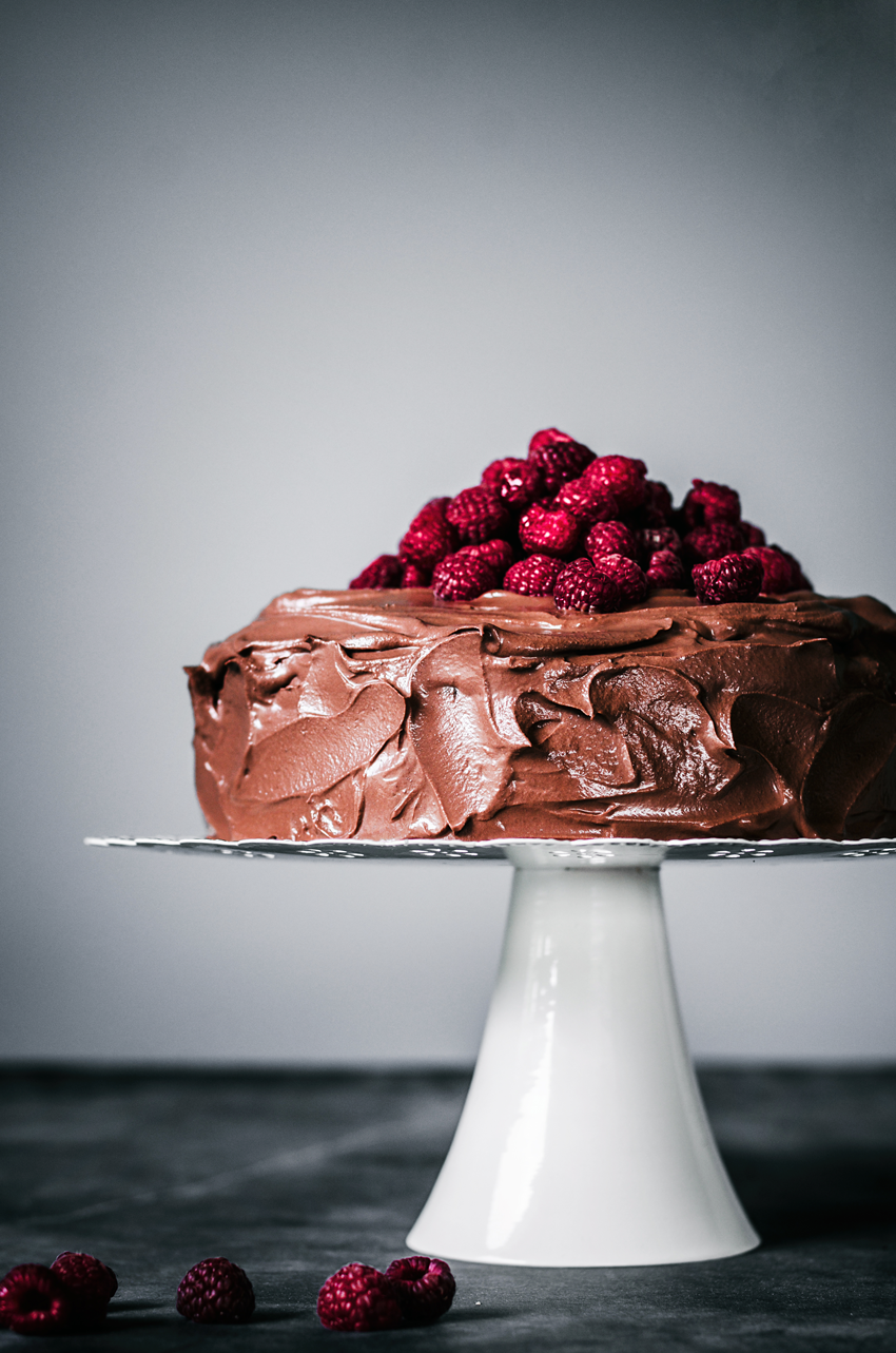 Chocolate ganache iced cake on white cake stand with pile of raspberries on top.
