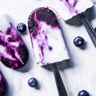 Four blueberry swirled coconut milk popsicles with spoons as handles.