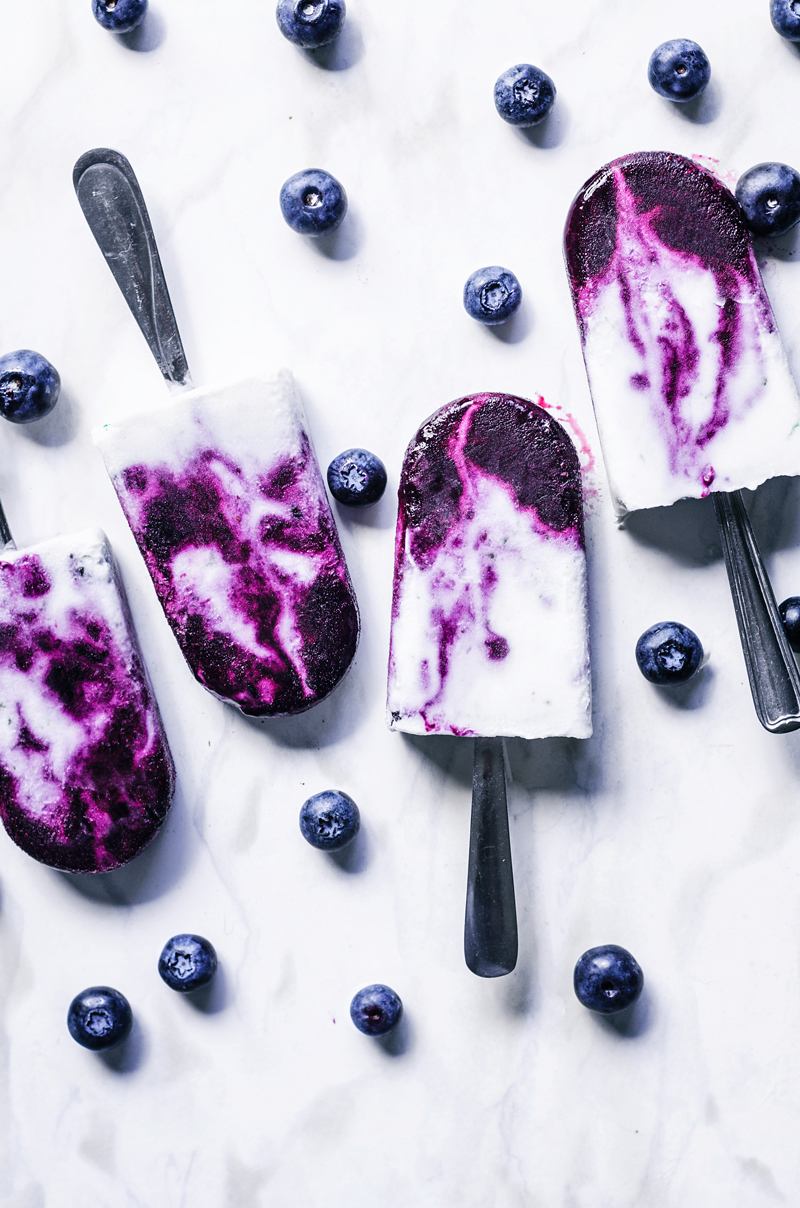 Blueberry swirl coconut milk popsicles with spoons for sticks.