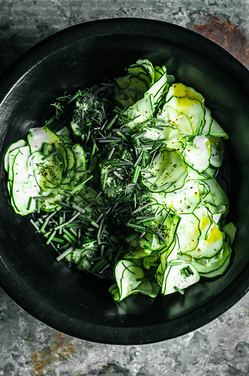 Very thinly sliced cucumbers in a large bowl topped with vinaigrette and herbs.