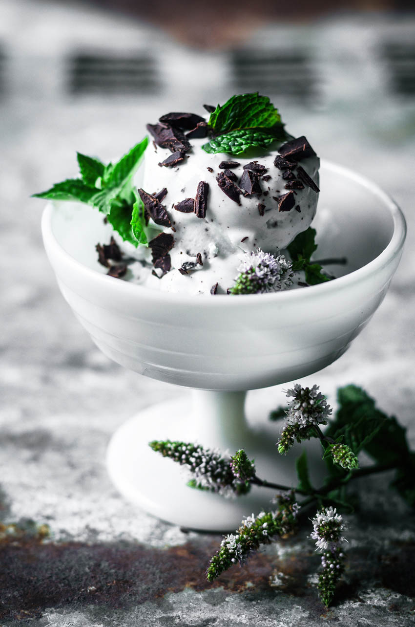 Vegan mint chocolate chip ice cream in a milk-glass coupe topped with more chocolate and mint leaves.