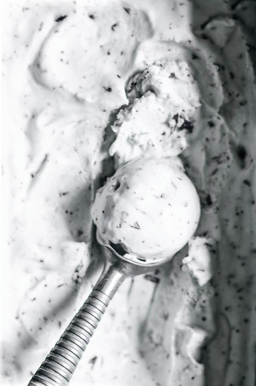 Close up of old metal ice cream scoop scooping vegan mint chocolate ice cream.