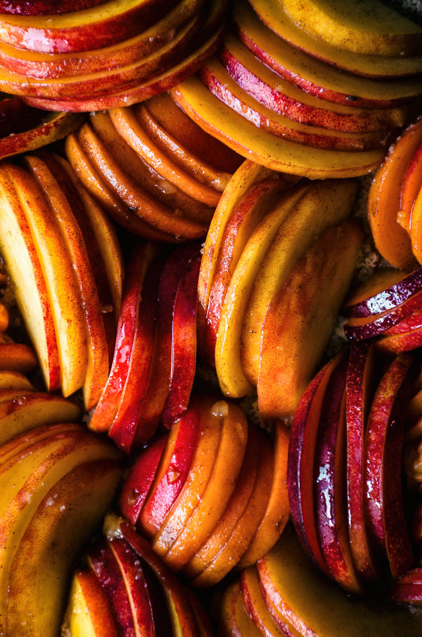 Close up of thinly sliced stone fruits arranged in a galette.