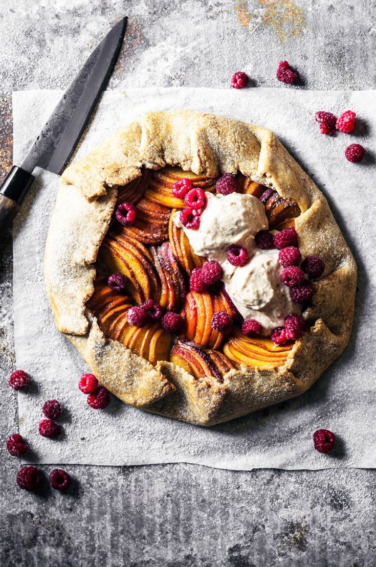 A peach and apricot galette with ice cream and raspberries on parchment paper.