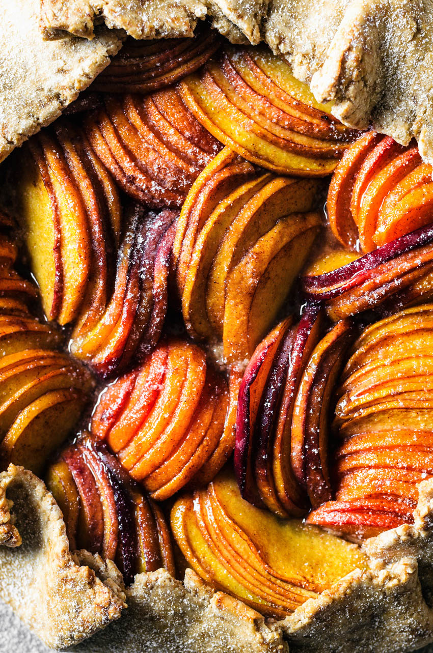 Close up of a stone fruit galette with thinly sliced fruit.