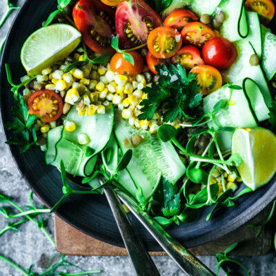 Salad with cucumber, corn, cherry tomatoes, and lime.
