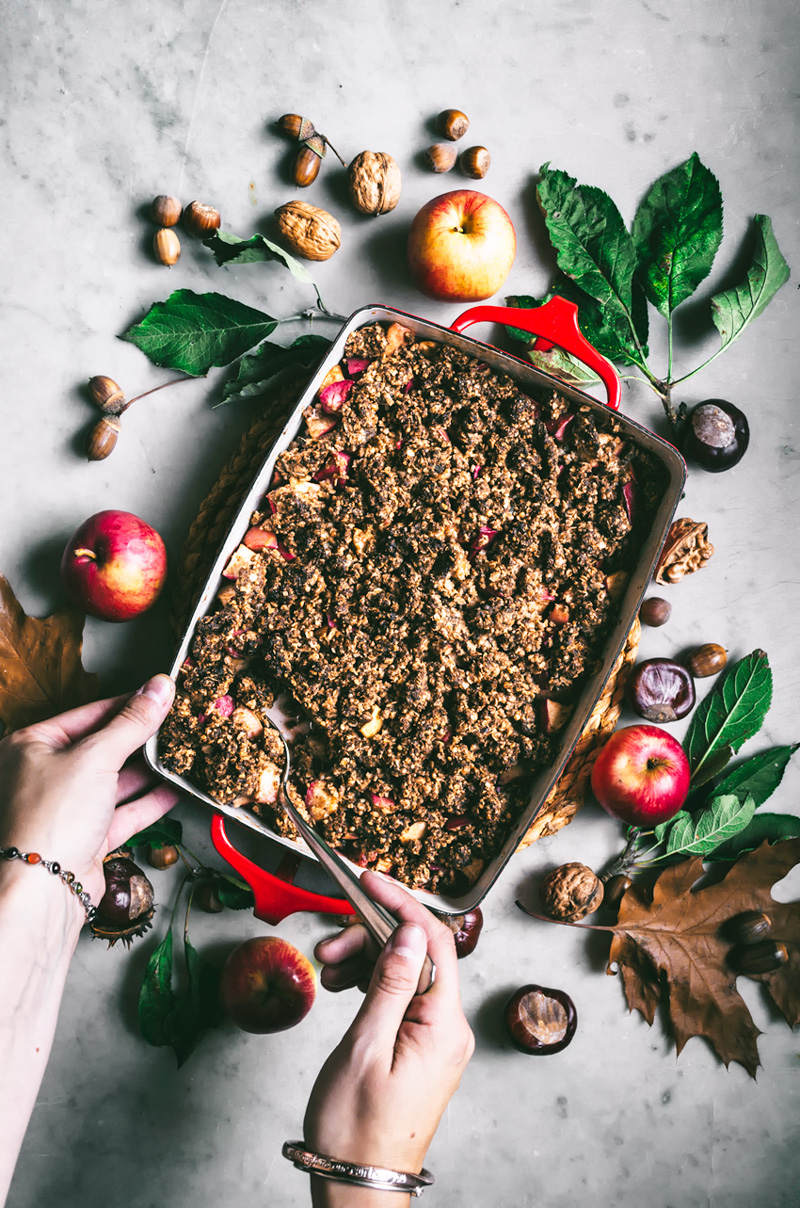 Woman taking serving of apple crumble from red baking dish.