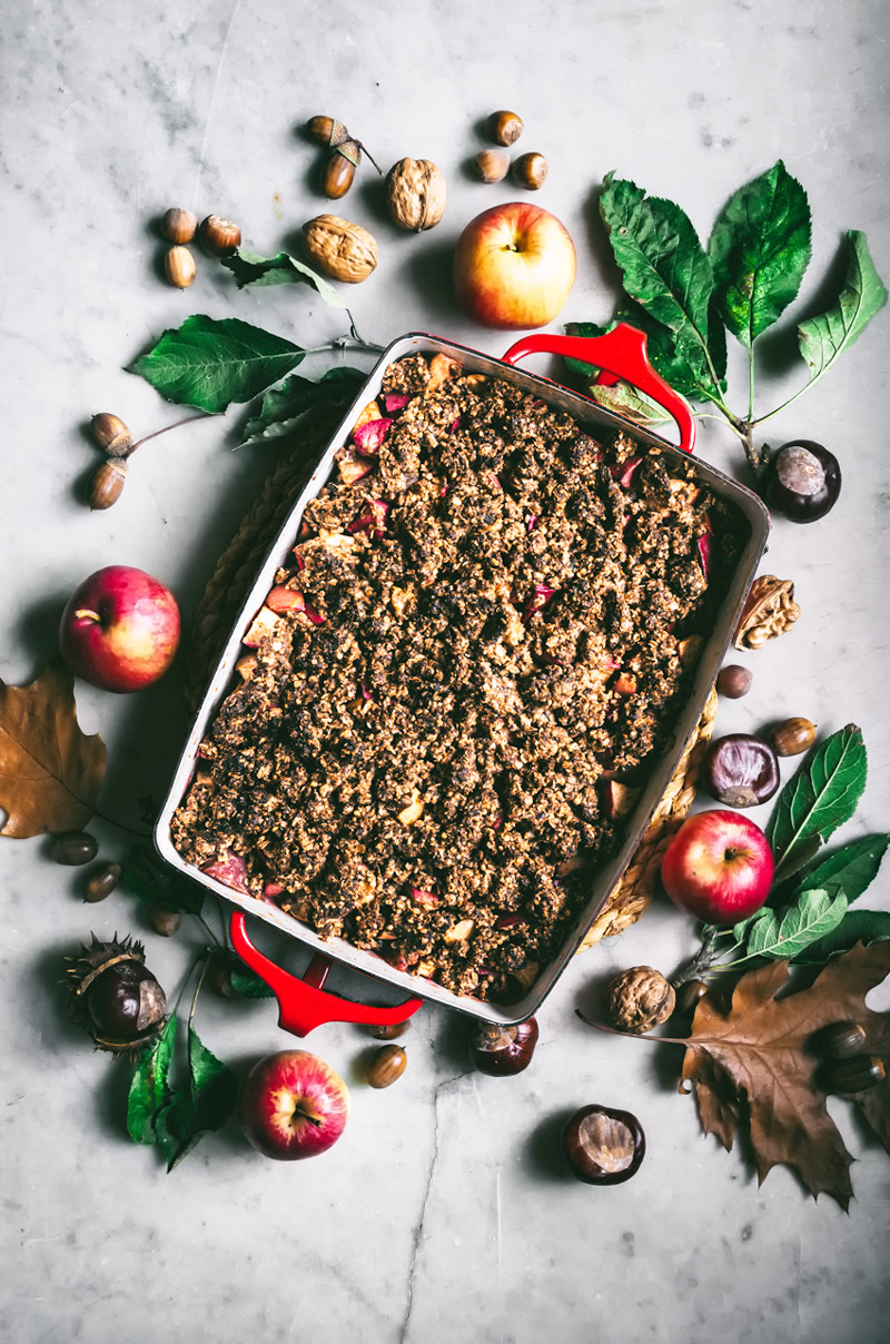 Hazelnut apple crumble in baking dish, surrounded by autumn leaves.