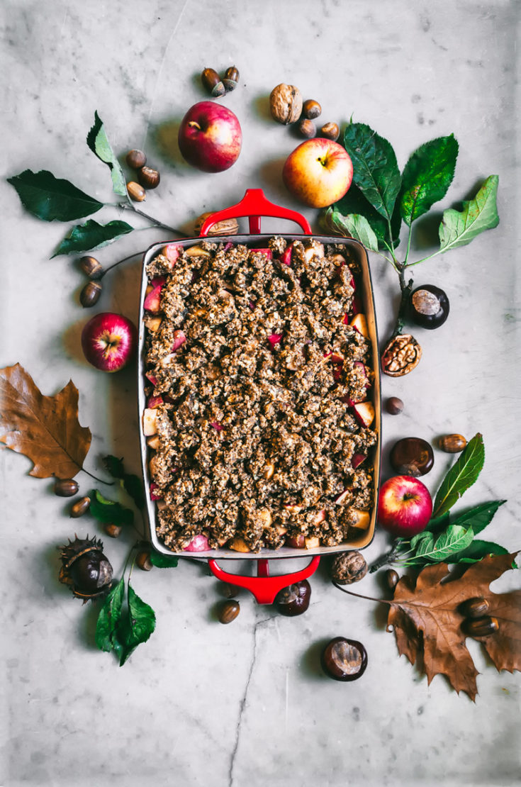 Hazelnut apple crumble in baking dish, surrounded by autumn leaves, unbaked.