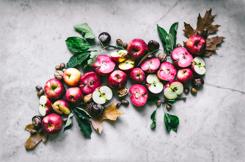 Cut and whole apples, both pink and white, with other fall items arranged on marble.