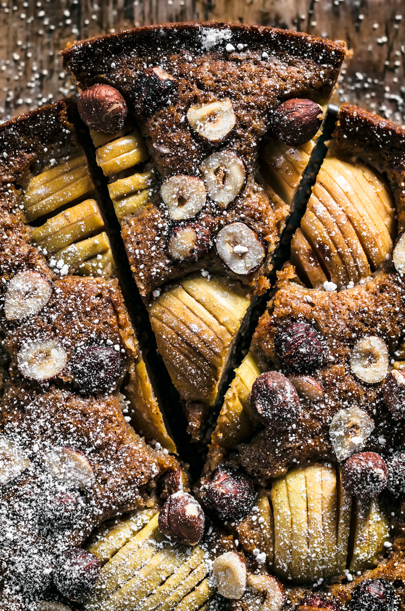 Apple hazelnut cake on dark wooden surface.