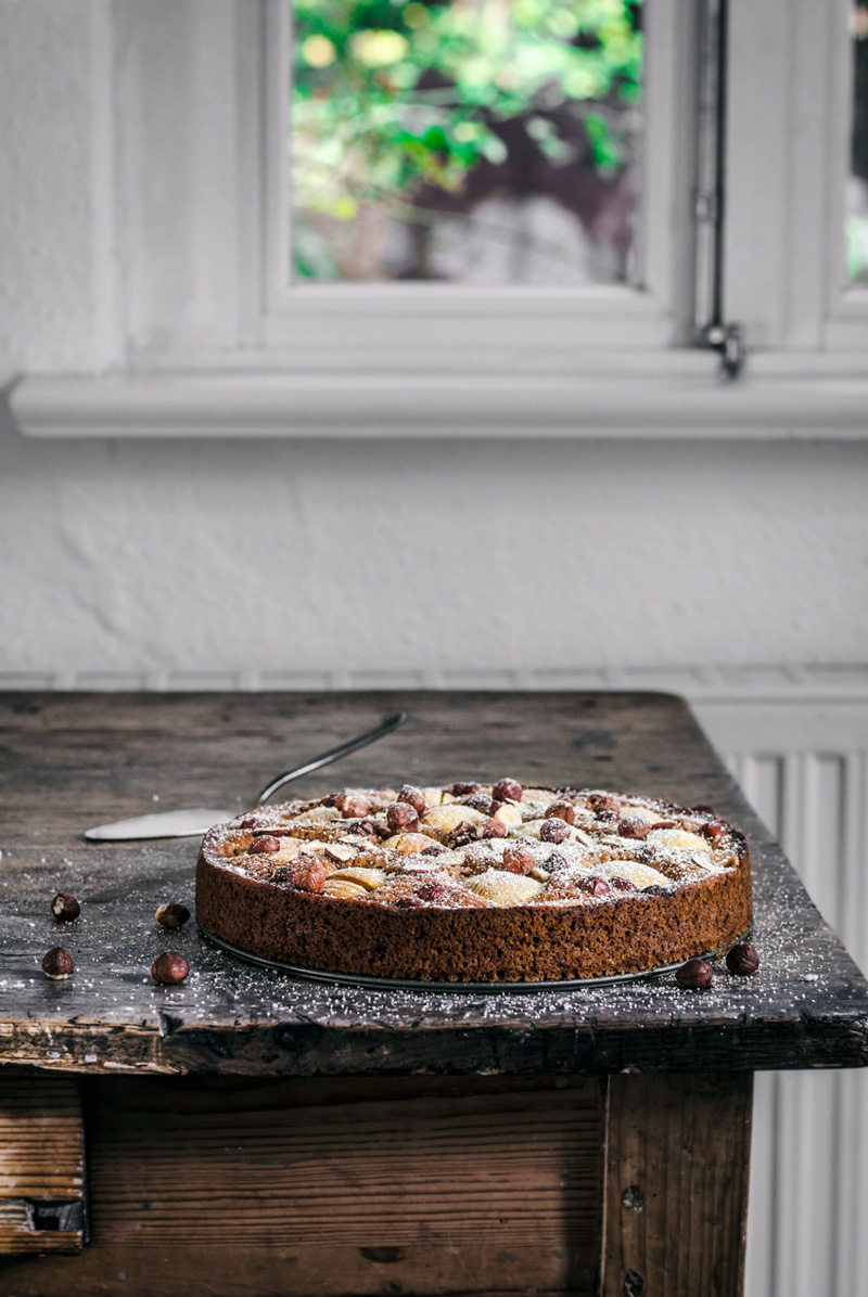 Apple hazelnut cake on dark wooden table with white wall in background.