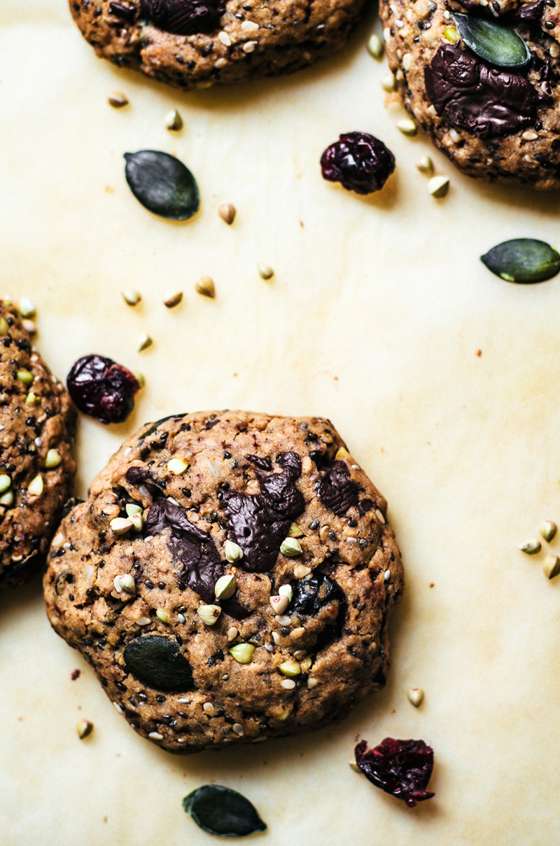 Buckwheat cookies with dried fruit and chocolate on parchment paper.
