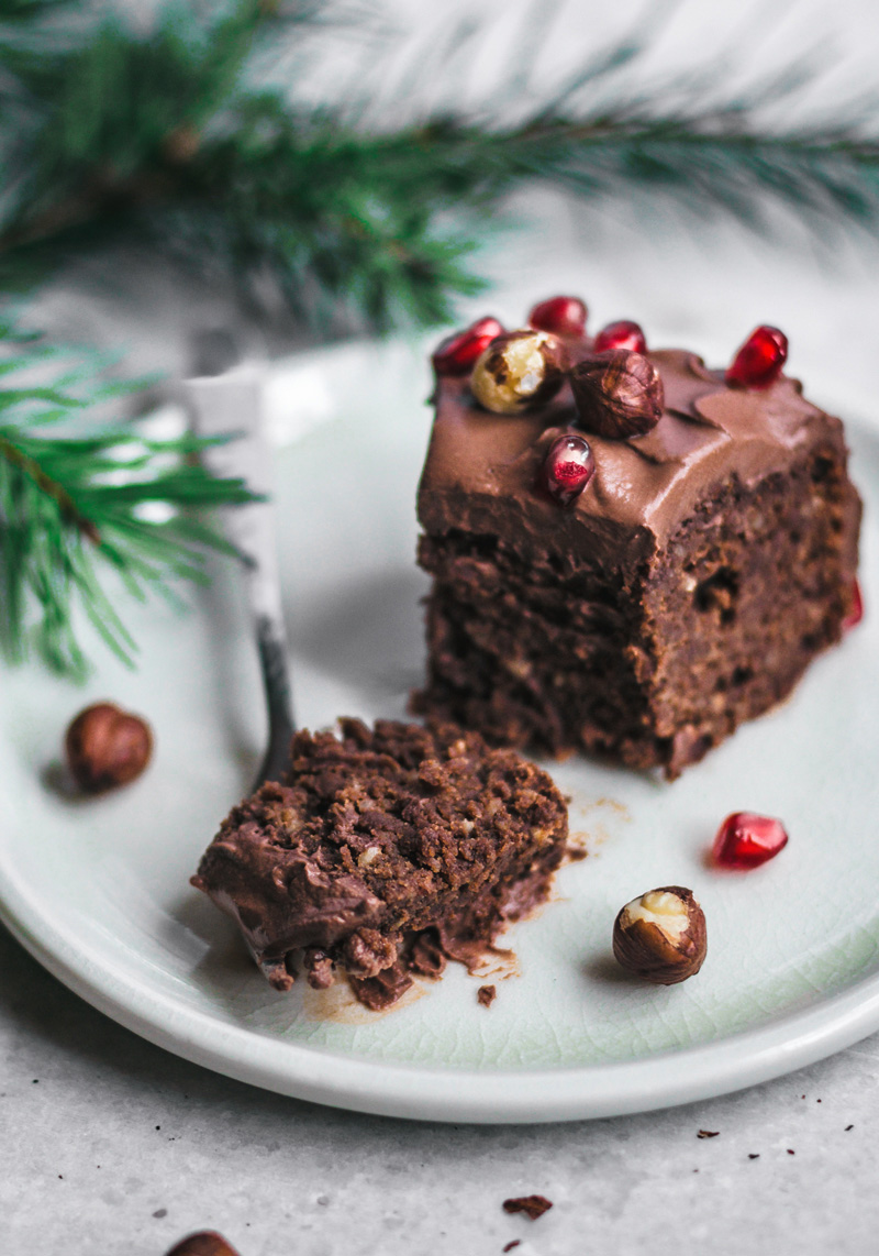 Slice of chocolate hazelnut cake topped with nuts and pomegranate, close up.