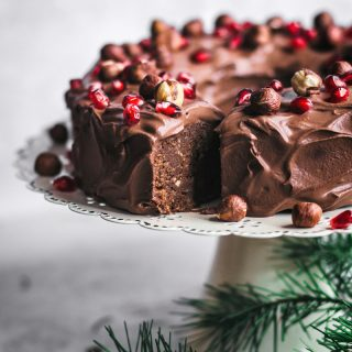 Bundt cake iced with chocolate ganache icing on a white cake stand, topped with nuts and pomegranate, one slice cut.