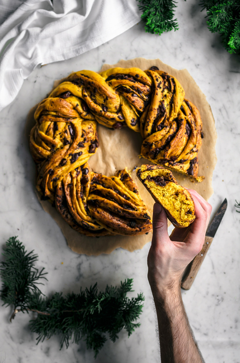 yellow saffron braided wreath bread with chocolate, on marble backdrop with hands holding a slice