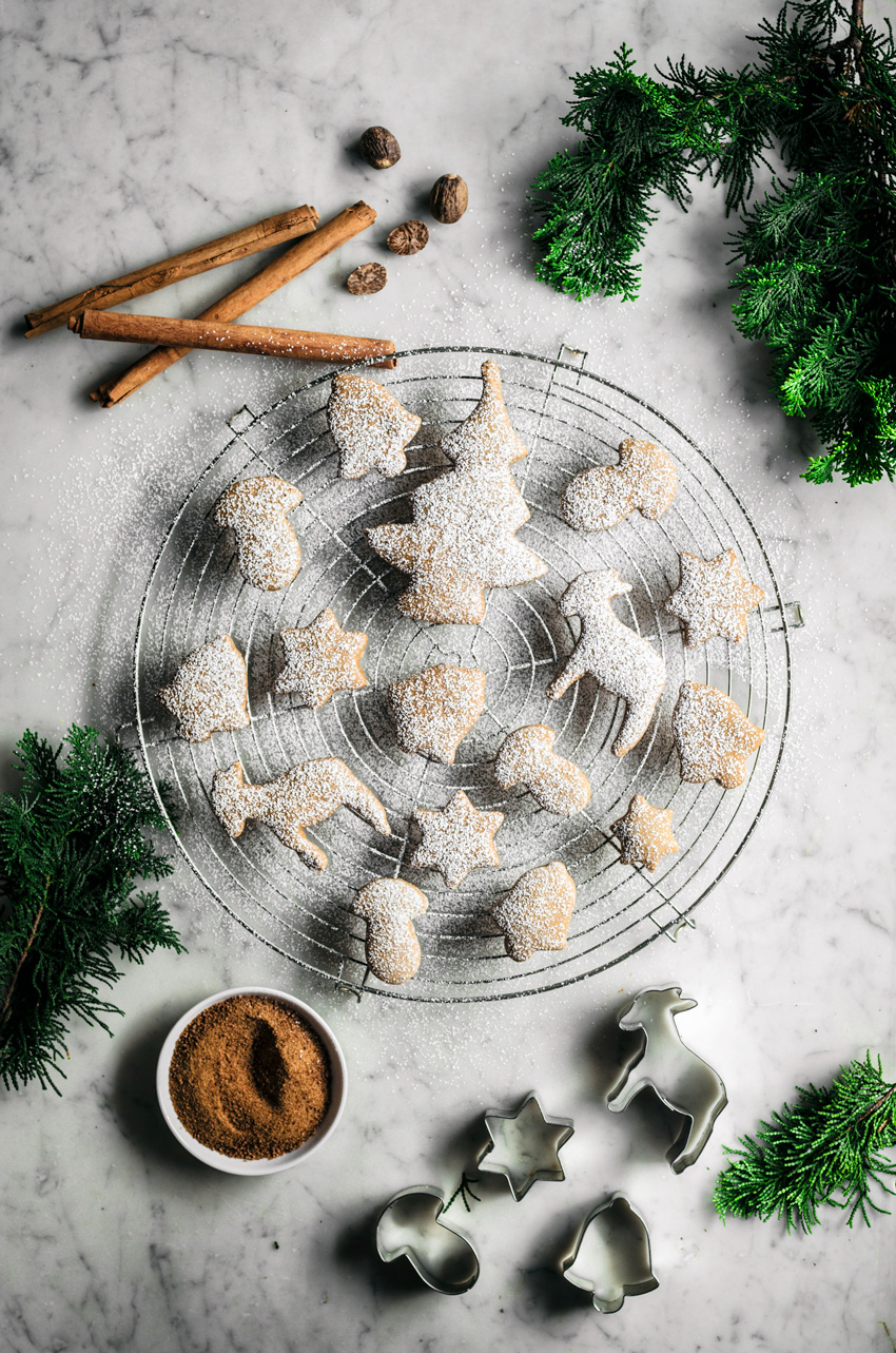 Spiced sugar cookie cut-outs shaped like trees, bells, mushrooms, and stars on a rack with spices and icing sugar.
