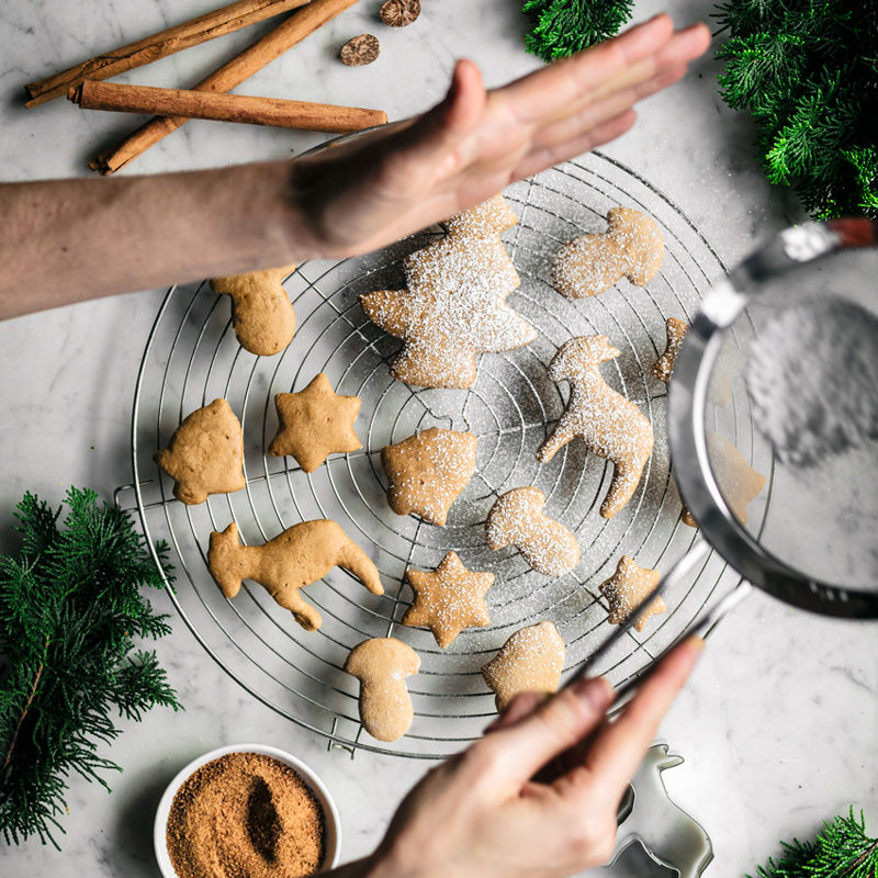 Spiced sugar cookie cut-outs shaped like trees, bells, mushrooms, and stars on a rack with spices and woman sprinkling icing sugar.