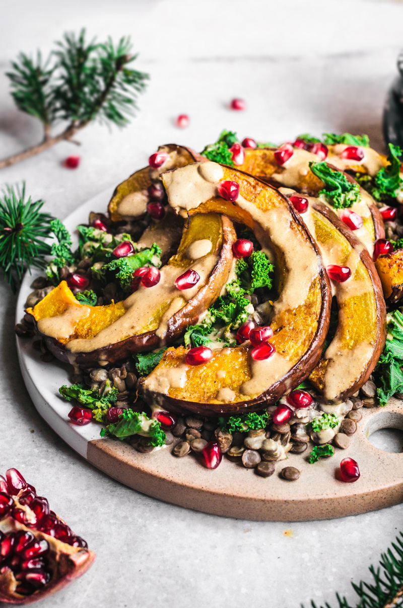 Roasted pumpkin salad with kale and lentils on white platter with creamy tahini dressing.