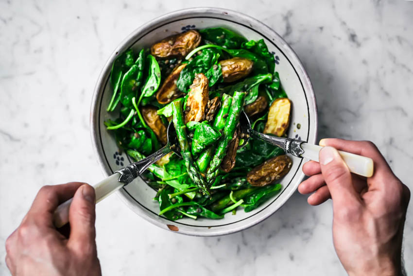 Man's hands using utensils to mix a potato lentil salad with asparagus and greens.