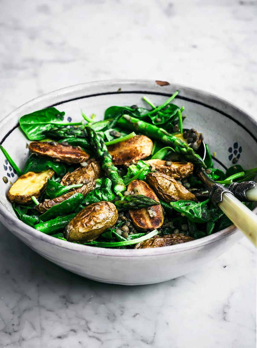 Roasted new potato and asparagus salad with lentils and greens in a large bowl.