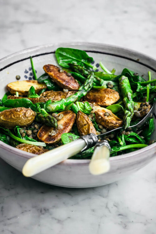 Potato asparagus salad in a large bowl with serving utensils.