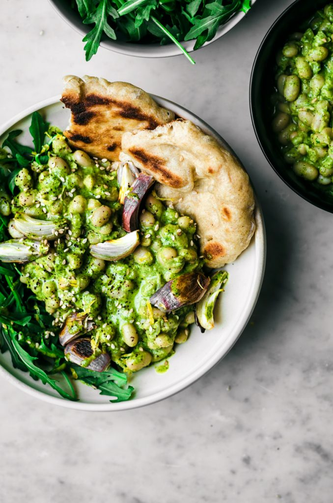 White bean salad with green herb sauce in white bowl, with naan and shallots