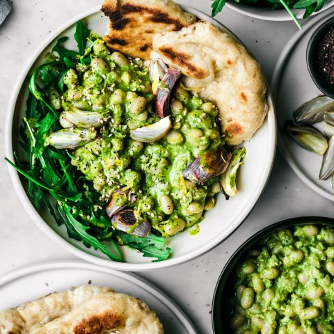 White bean salad with green sauce in bowl, top down view, surrounded by dishes of naan, more beans, shallots, and rucola