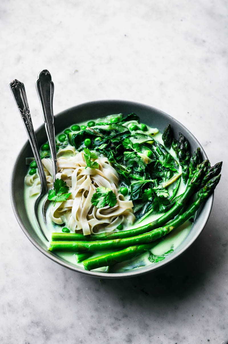Front view of rice noodles in a coconut milk broth with green vegetables.