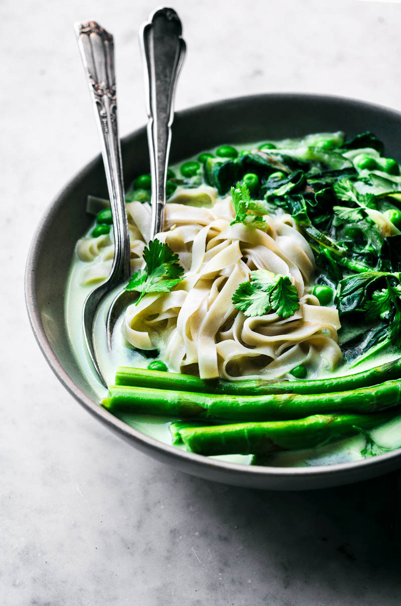 Close up of rice noodles in a bowl with cutlery, green vegetables, and broth.