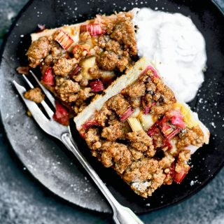 Two squares of rhubarb cake with crumble topping and yogurt on a plate.
