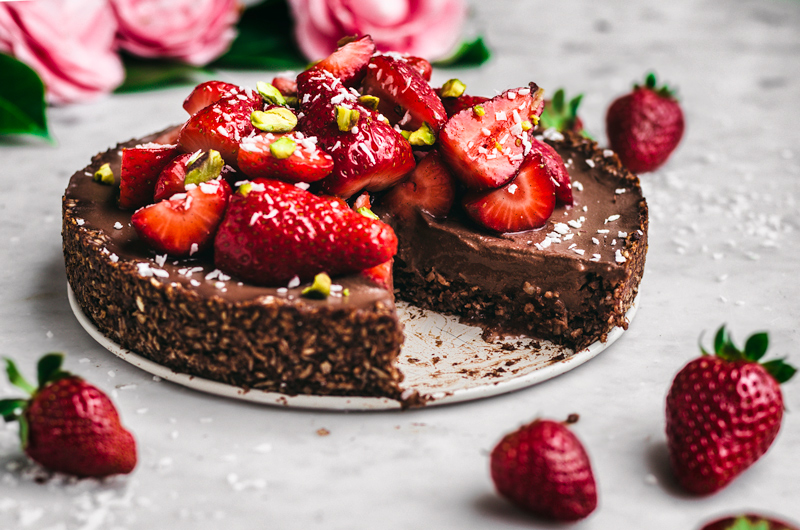 Chocolate coconut pie front view with fresh strawberries halves, shredded coconut, and pistachios