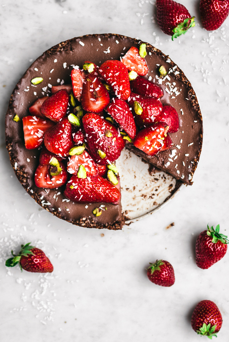 Chocolate coconut pie top view with fresh strawberries halves, shredded coconut, and pistachios, one slice missing
