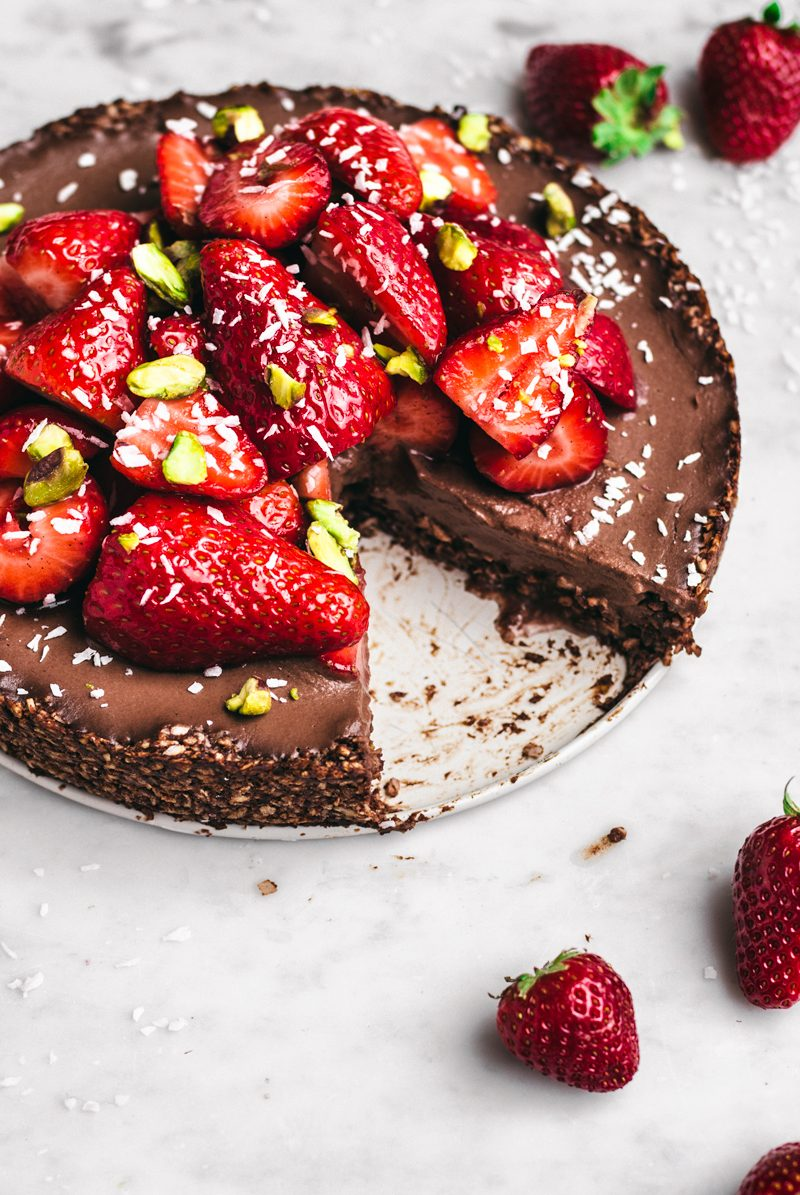 Chocolate coconut pie 30 degree angle with fresh strawberries halves, shredded coconut, and pistachios, one slice missing