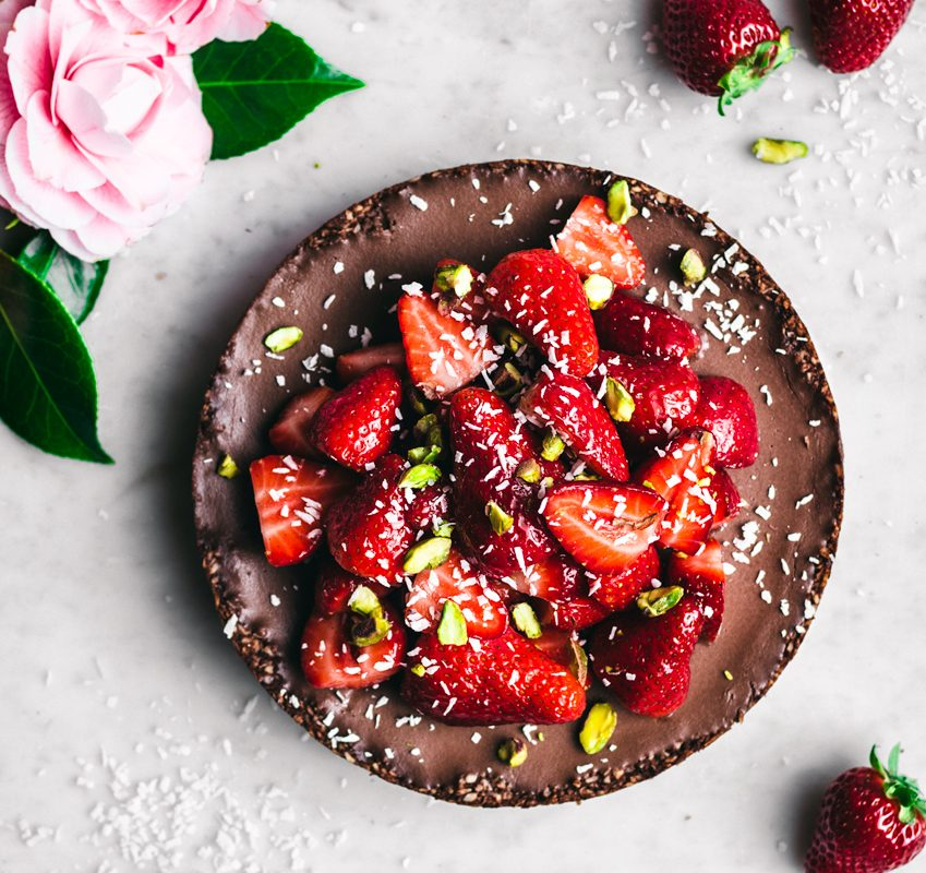Chocolate coconut pie top view with fresh strawberries halves, shredded coconut, and pistachios, pink camilla flowers in top left corner