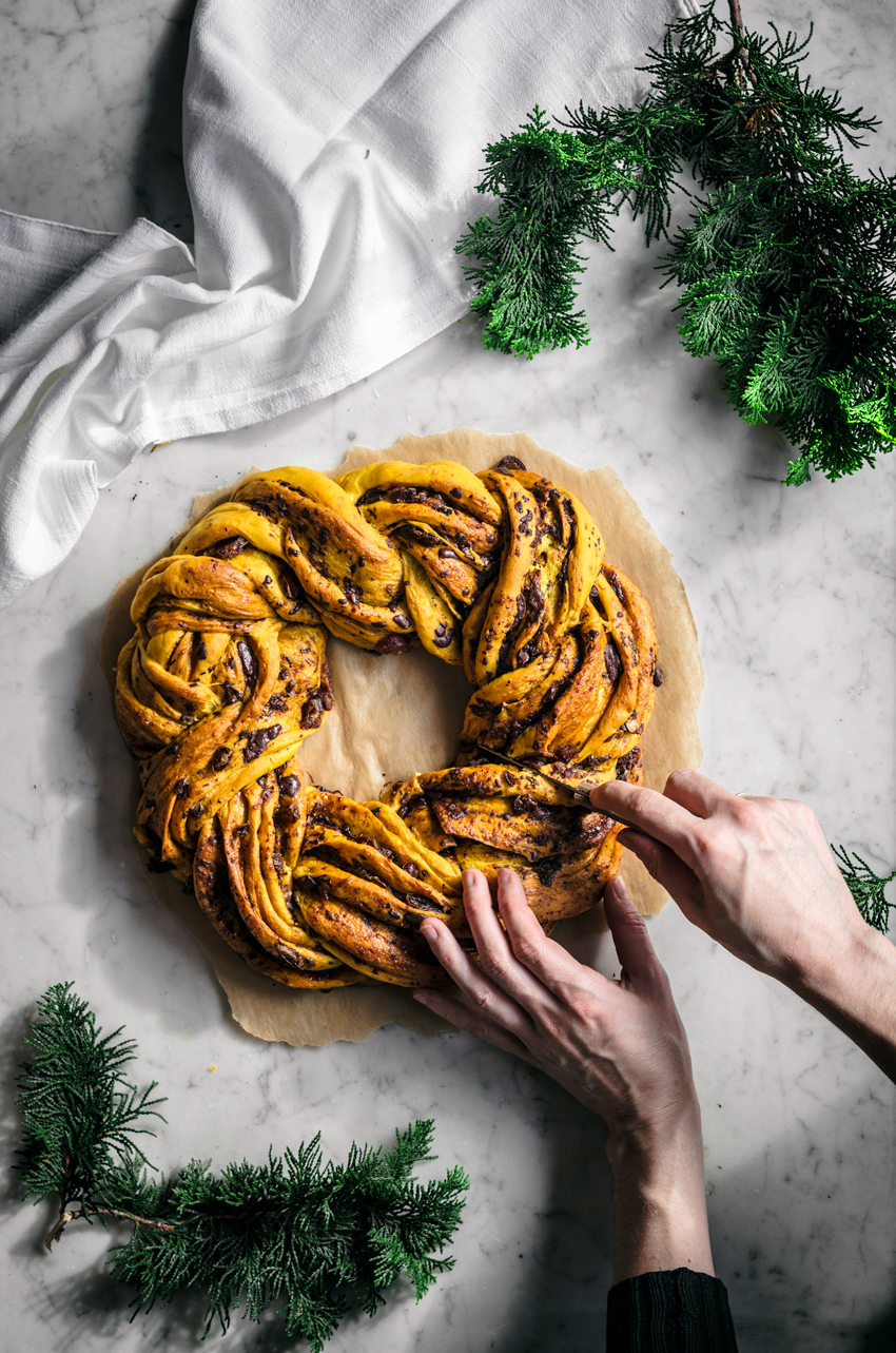 yellow saffron braided wreath bread with chocolate, on marble backdrop with hands cutting a slice