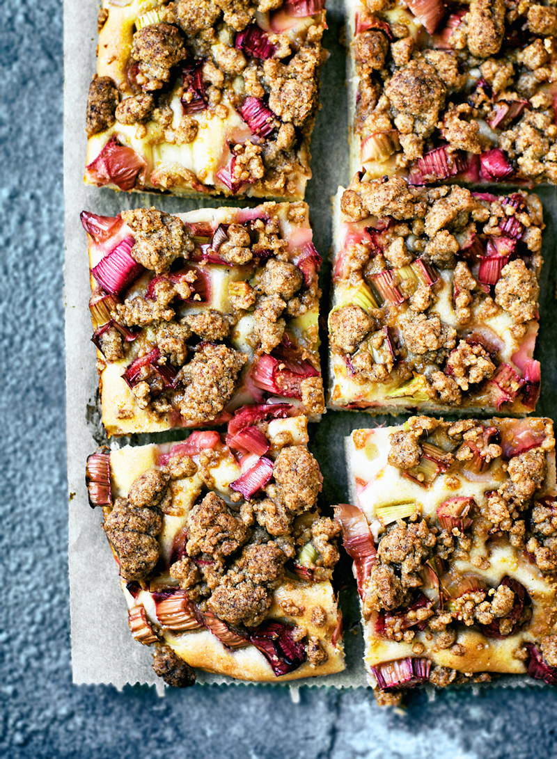 rhubarb streusel cake on blue grey background, cut into squares, top view