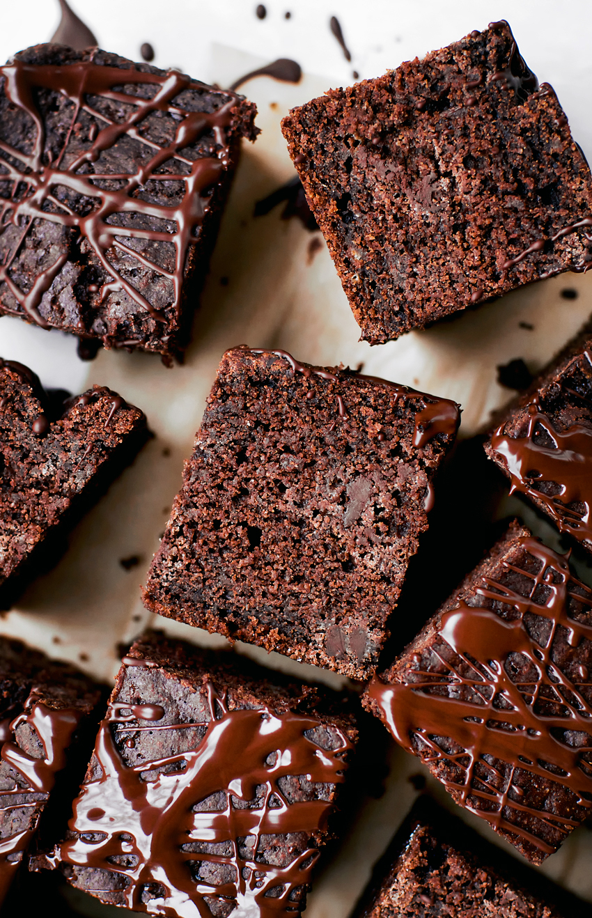 chocolate cake, cut into squares on parchment paper