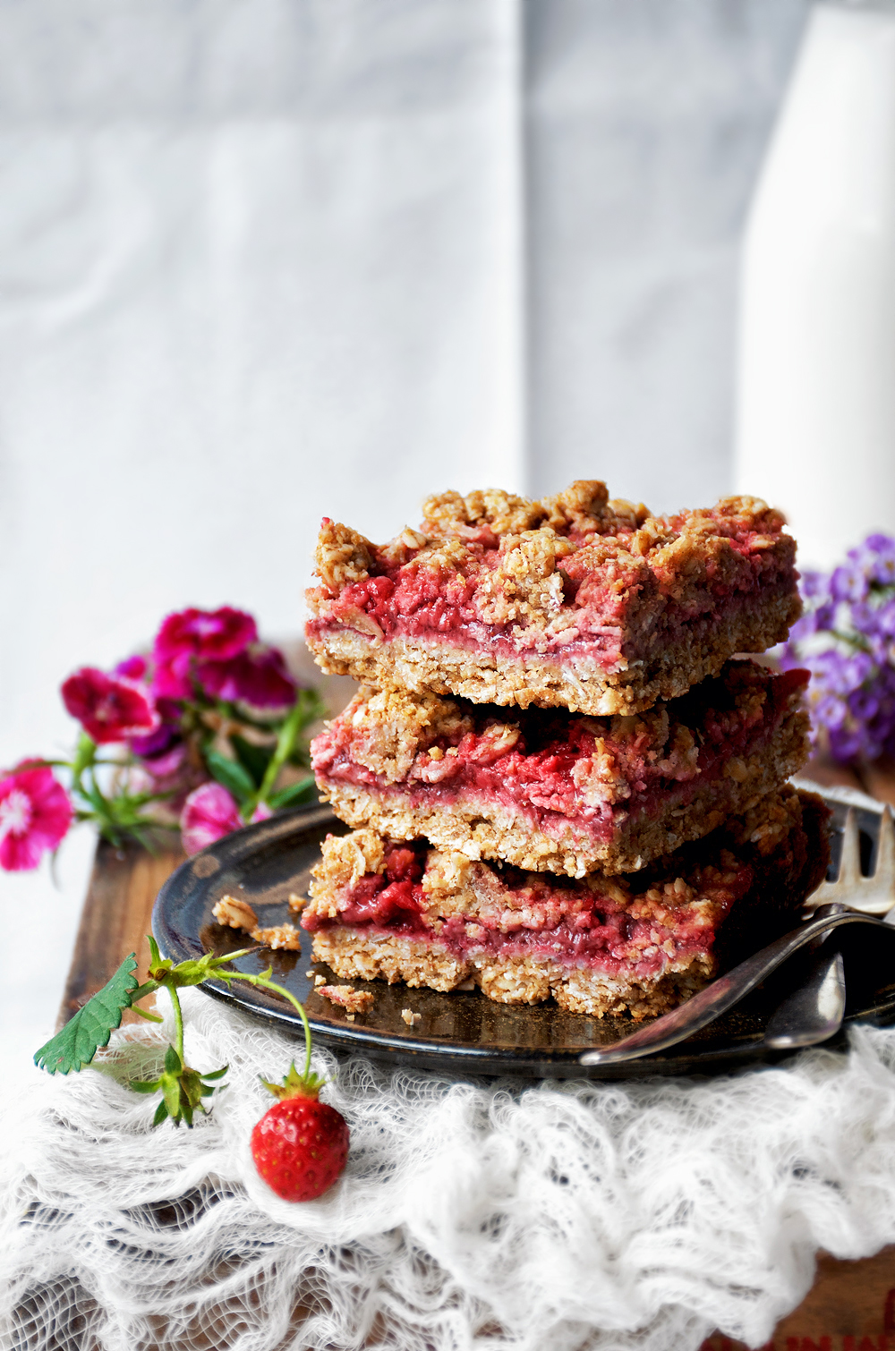 strawberry crumble bars, stack of three, front view, with flowers in background