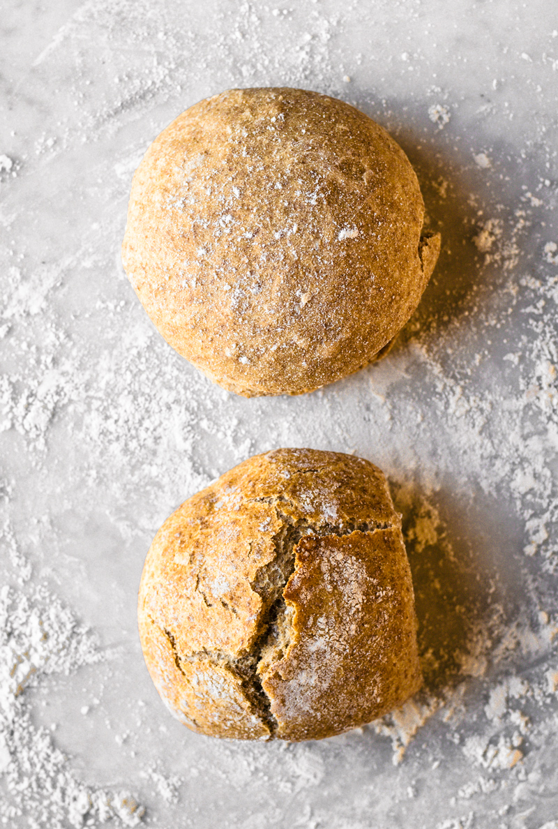 Two buns on marble backdrop with flour, one smooth and one with cracked top