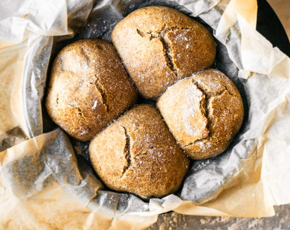 Four crusty buns with cracked tops in parchment lined cast iron pan, on marble surface