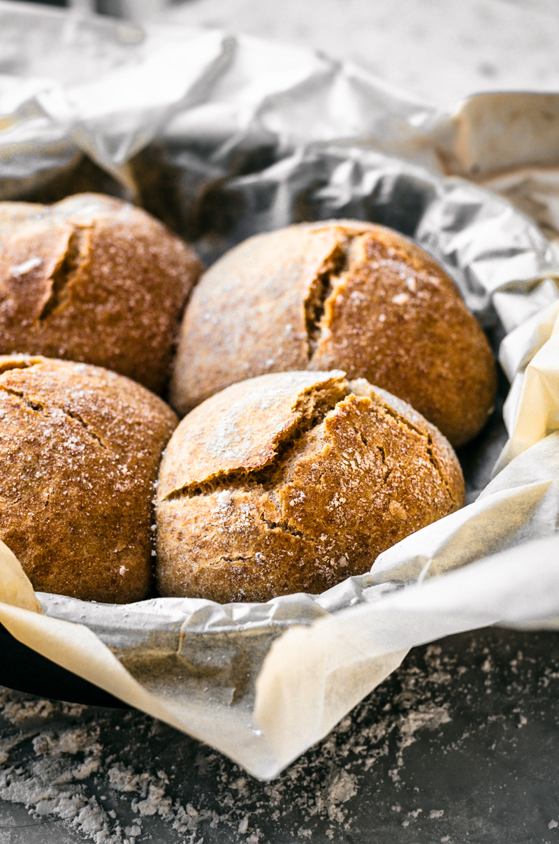 Four crusty buns with cracked tops in parchment lined cast iron pan, on marble surface, front view with backlighting