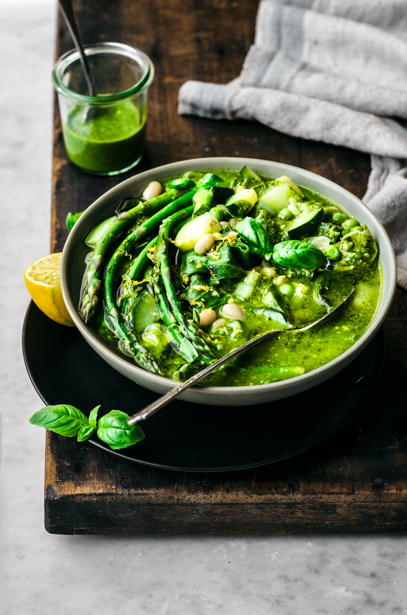 Green minestrone soup with asparagus, white beans, and basil in bowl with spoon sitting on plate, with dark wood and marble backdrop, front view