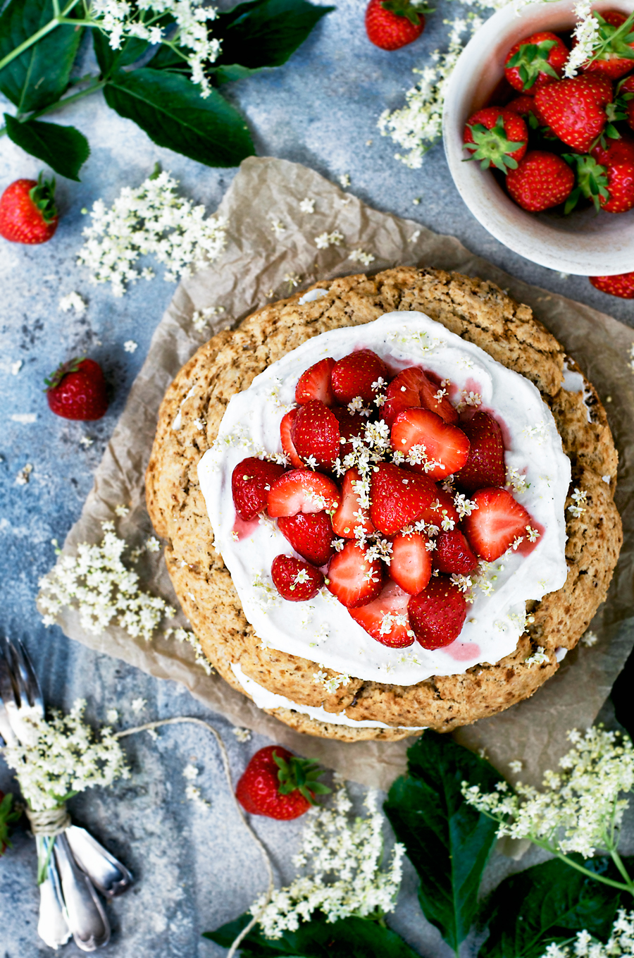 giant scone cake topped with coconut whipped cream, strawberries, and elderflower blossoms