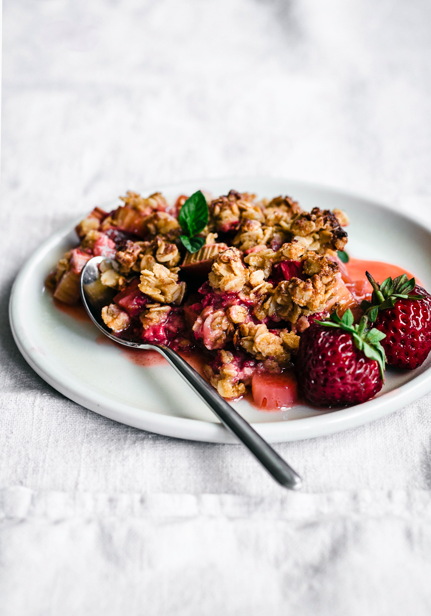 strawberry rhubarb crumble, front view, on white linen cloth and white plate