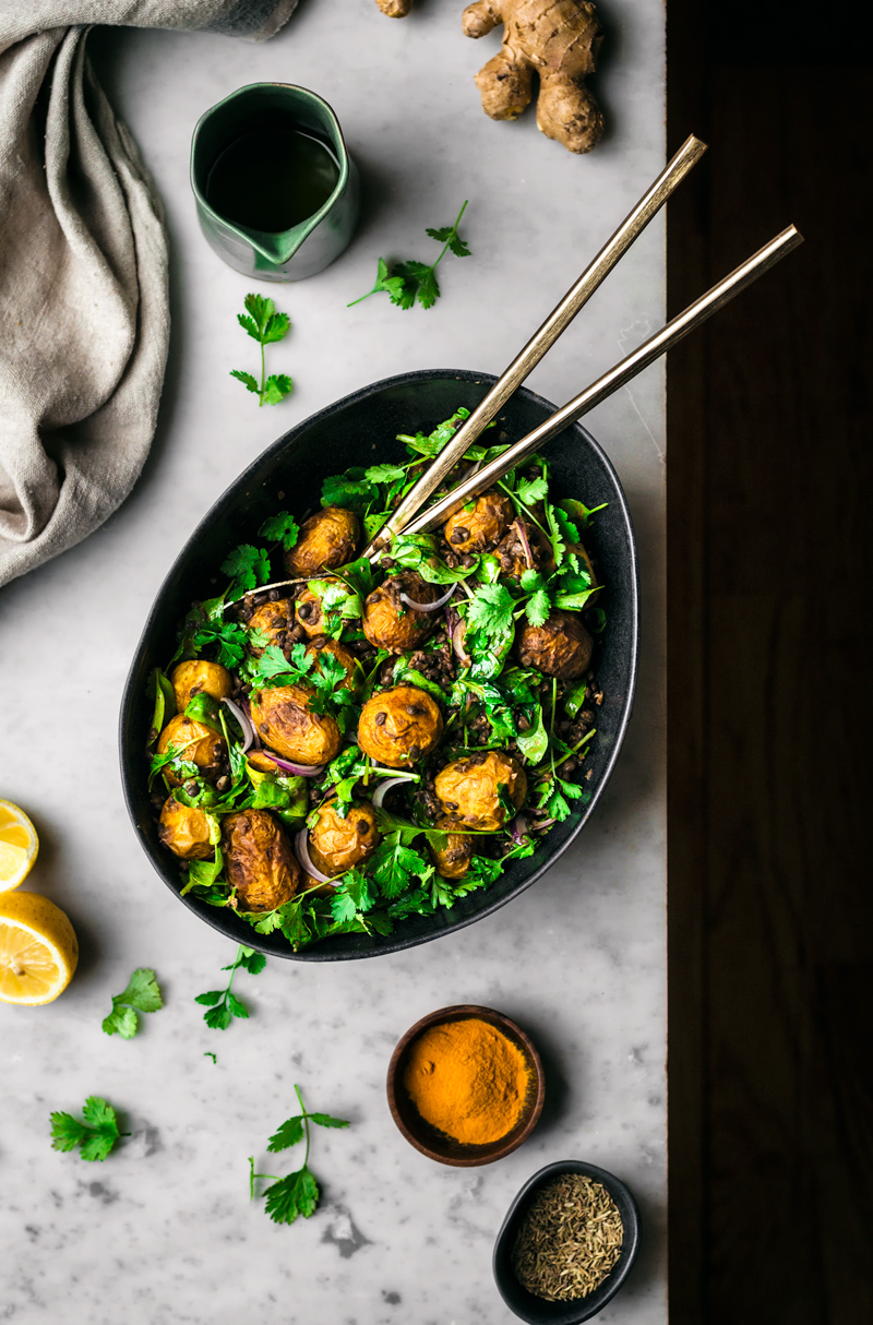 Curry potato salad with greens in black bowl, top view.