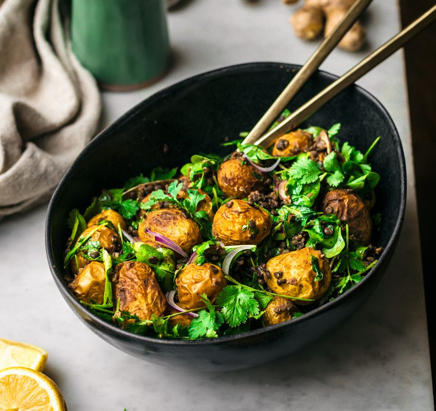 Curry potato salad with greens in black bowl, front view.