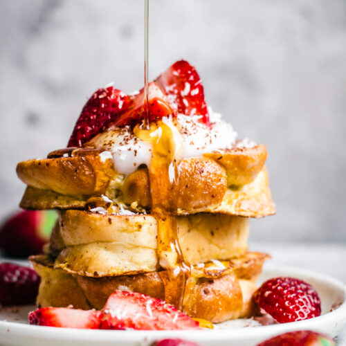 Stack of three pieces of challah french toast, with strawberries and maple syrup.